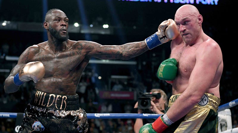 Deontay Wilder delivers a left hook to Tyson Fury during their heavyweight title boxing match in December 2018.