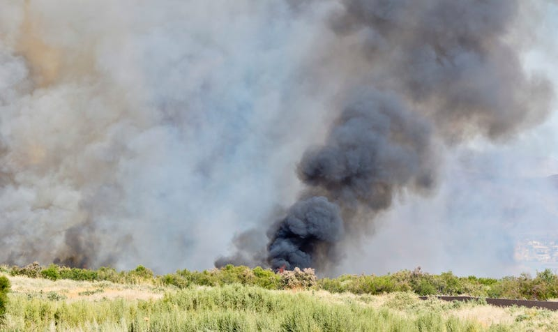 A wildfire burns in a desert area