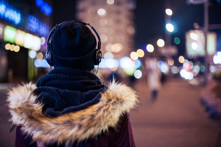 woman in coat wearing headphones