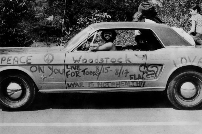 A music fan at Woodstock pop festival in his car covered in anti-war slogans for love and peace.