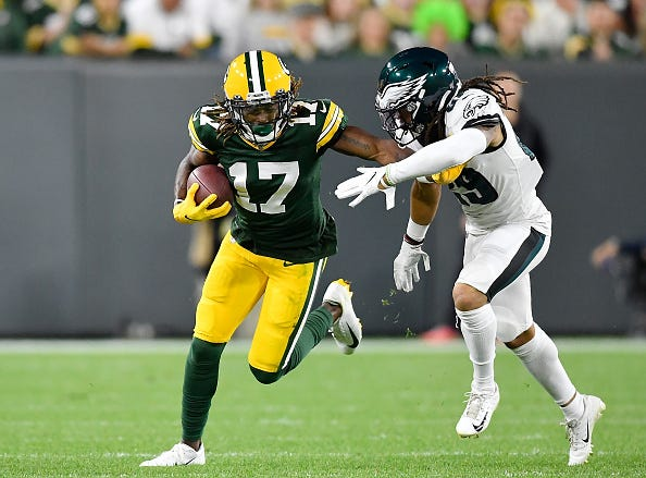 Davante Adams stiff arms and Eagles defensive back.