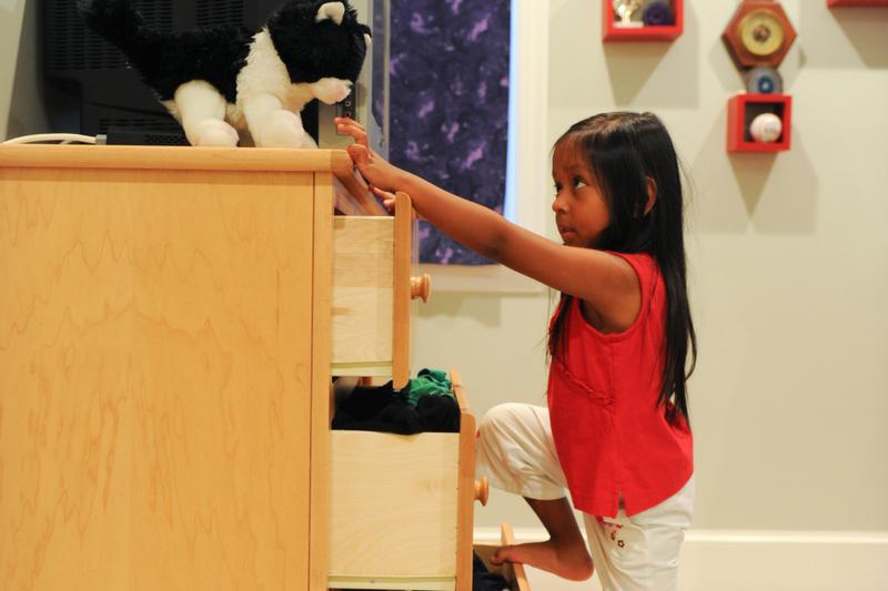A child begins to climb a dresser