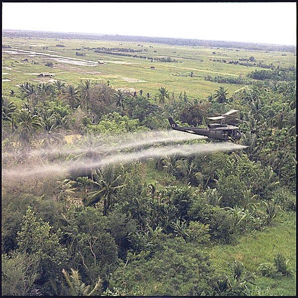 A helicopter sprays herbicide over Vietnam.