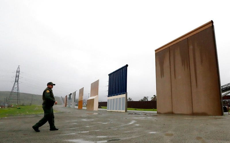 Border Patrol agent Vincent Pirro walks towards prototypes for a border wall in San Diego.