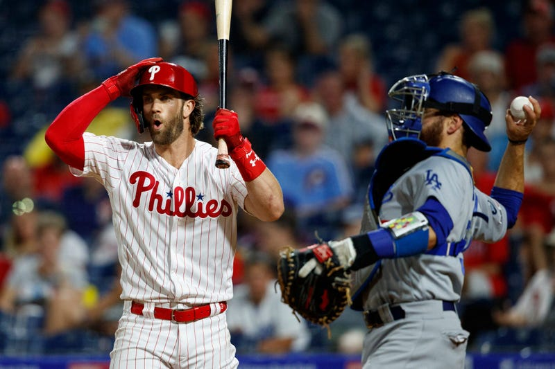 Philadelphia Phillies' Bryce Harper, left, reacts after striking out against Los Angeles Dodgers relief pitcher Julio Urias during the fourth inning of a baseball game Wednesday, July 17, 2019, in Philadelphia.