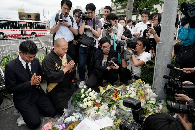 Japanese Diet member, Kenta Izumi, left, and Buddhist monk, Matsumoto Genkun, pay respects at a makeshift memorial site in front of burned Kyoto Animation Studio building, background left, Friday, July 19, 2019, in Kyoto, Japan.