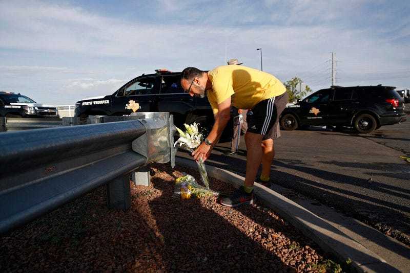 A man leaves flowers near the scene of a mass shooting at a shopping complex Sunday, Aug. 4, 2019, in El Paso, Texas.