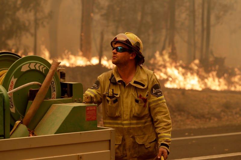 A Forest Corporation worker manages a fire hose as he battles a fire near Moruya, Australia, Saturday.
