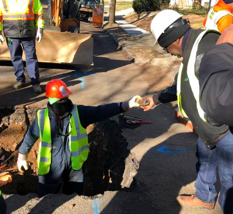 A worker hands a piece of lead pipe to a colleague as they work to remove water service lines Thursday, Jan. 9, 2020, in Trenton, N.J.