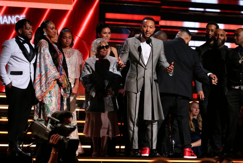 John Legend, center, DJ Khaled and members of Nipsey Hussle's family accept the award for best rap/sung performance at the 62nd annual Grammy Awards on Sunday, Jan. 26, 2020, in Los Angeles.