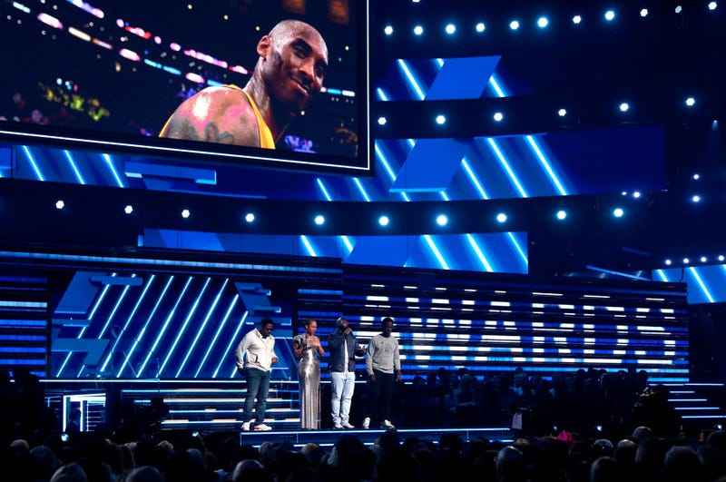 """Alicia Keys, second left, and members of Boys II Men, from left, Nathan Morris, Wanya Morris and Shawn Stockman, sing """"It's So Hard to Say Goodbye to Yesterday"""" during a tribute to the late Kobe Bryant, seen on screen, at the 62nd annual Grammy Awards."""