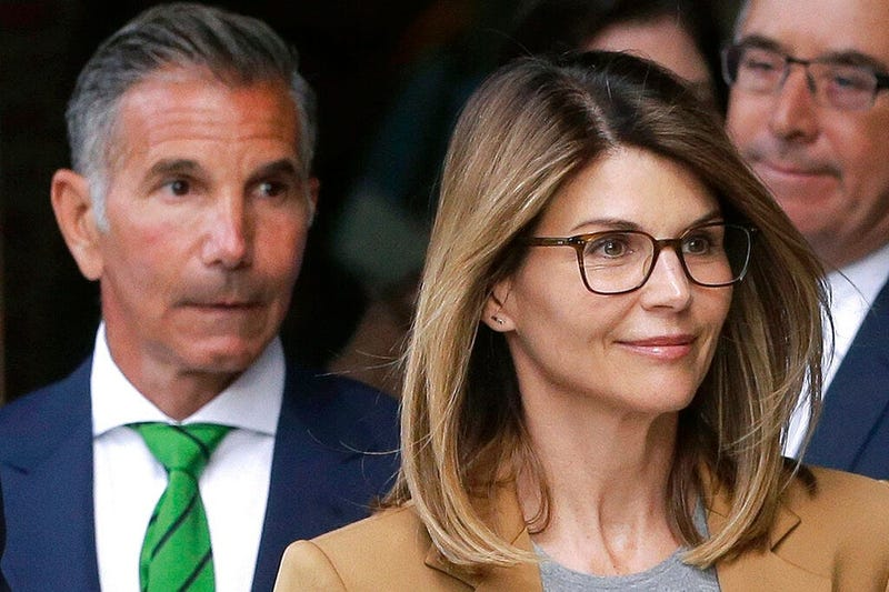 actress Lori Loughlin, front, and husband, clothing designer Mossimo Giannulli, left, depart federal court in Boston after facing charges in a nationwide college admissions bribery scandal. The famous couple pleaded guilty to charges in May 2020, and are