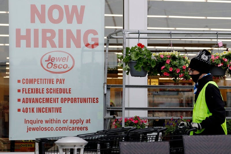 A man pushes carts as a hiring sign shows at a Jewel Osco grocery store in Deerfield, Ill., Thursday, April 23, 2020. Friday, Dec. 4. (AP Photo/Nam Y. Huh)