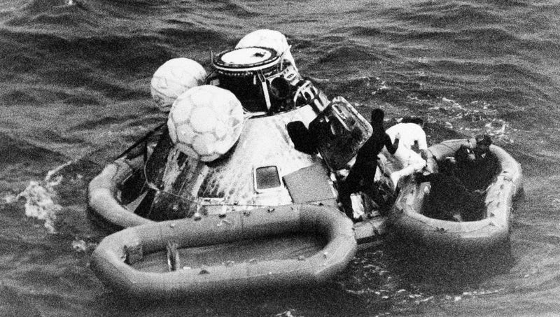In this Dec. 27, 1968 file photo, divers help recover the Apollo 8 crew from their capsule after splashdown in the Pacific Ocean.