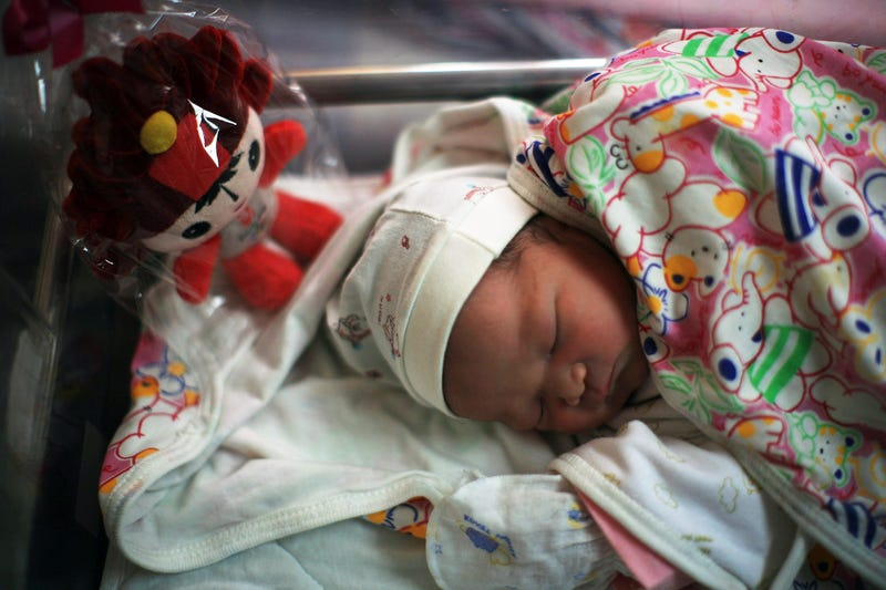 BEIJING - AUGUST 08: A Chinese baby sleeps next to a Beijing Olympic Mascot Fuwa at the Beijing Haidian maternal and child healthcare hospital after being born on August 8, 2008 in Beijing, China. There were 50 babies born at the hospital, about 60 percen