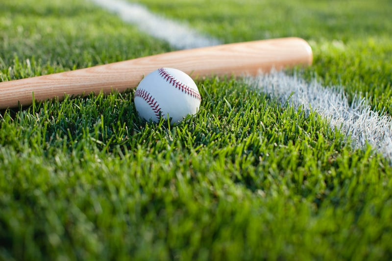Baseball and bat on grass field with white stripe