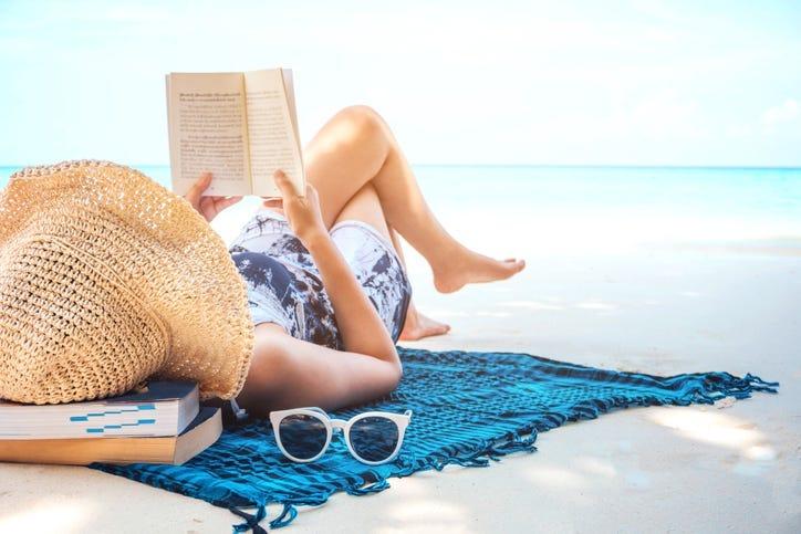 woman sunbathing on beach with belongings around her