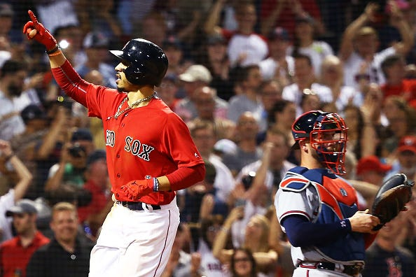 Mookie Betts celebrates scoring a run against the Atlanta Braves.