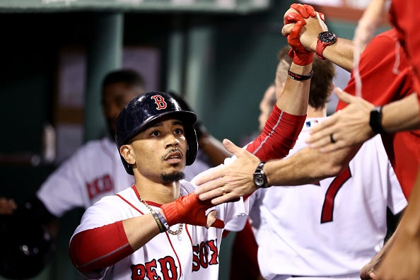 Mookie Betts celebrates with teammates in a game against the Cardinals.