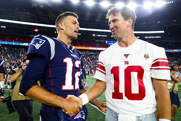 Tom Brady greets Giant quarterback Eli Manning