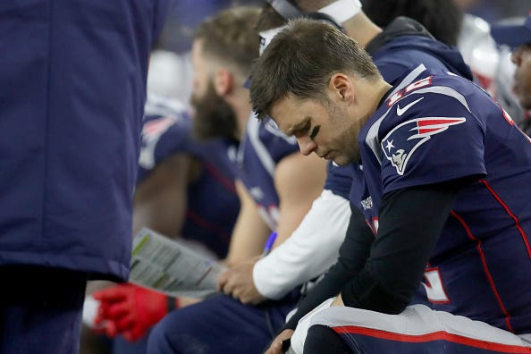 Tom Brady sits on the bench during the Patriots' 2019 Wild Card game.