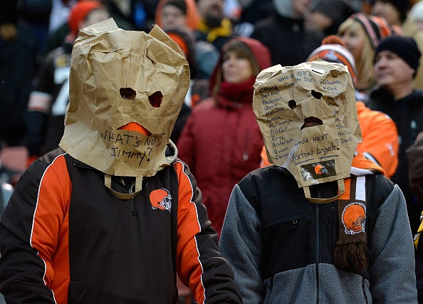 Embarrassed Browns fans hide their faces during a game.