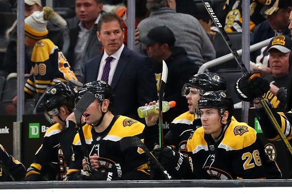 Bruins players watch from the bench during a game against the Hurricanes.