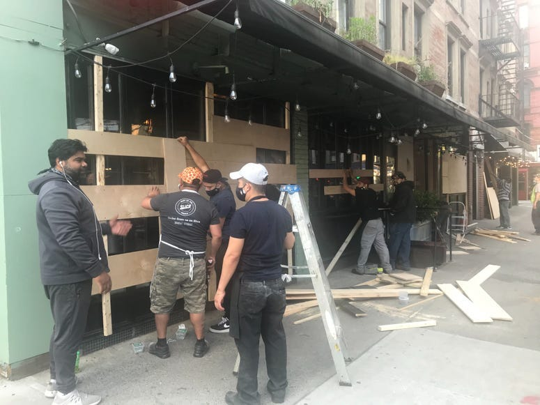 7:40 p.m. Restaurant workers board up the windows of an eatery on the Lower East Side.