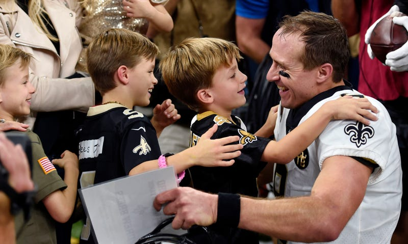 New Orleans Saints quarterback Drew Brees (9) greets his family after breaking the NFL all-time passing yards record in the first half of an NFL football game against the Washington Redskins in New Orleans, Monday, Oct. 8, 2018.