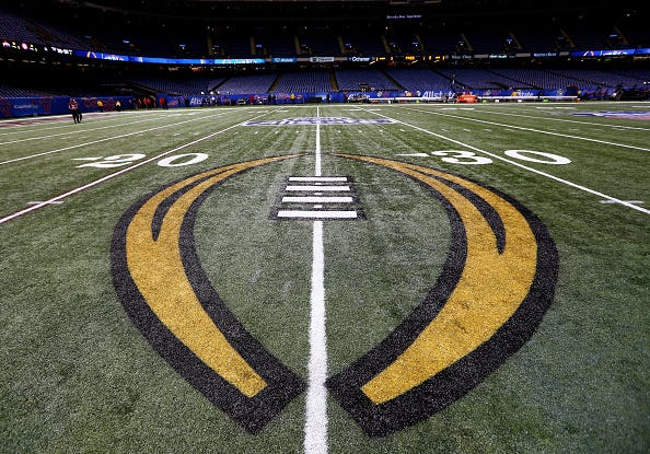 The College Football Playoff logo on the field of the Superdome.