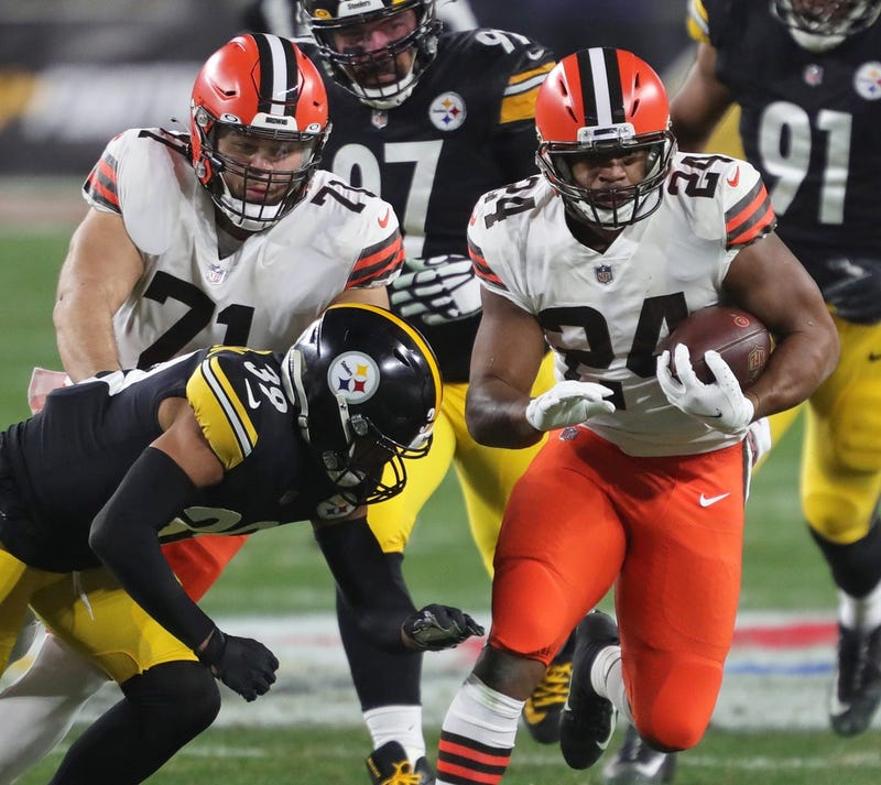 Cleveland Browns running back Nick Chubb rushes for a first down as Cleveland Browns offensive tackle Jedrick Wills blocks during the second half of an NFL wild-card playoff football game, Sunday, Jan. 10, 2021, in Pittsburgh, Pennsylvania.