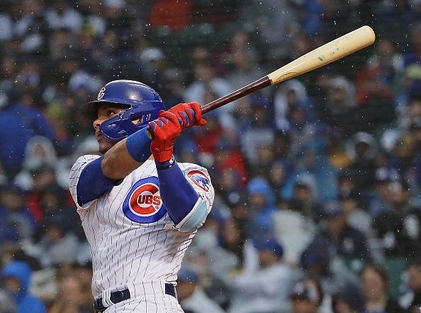 Willson Contreras watches a ball he hit through the rain.