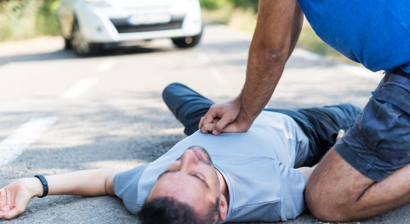 A man performs CPR on a another man laying on the ground