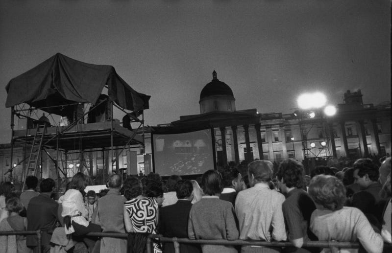 Crowds watching pictures of the first landing on the moon on a large screen in Trafalgar Square, London.