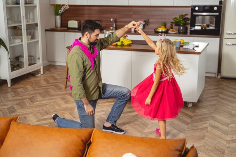 Smiling father dancing with his daughter
