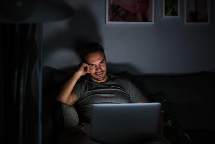 Man in dark room binge watching TV