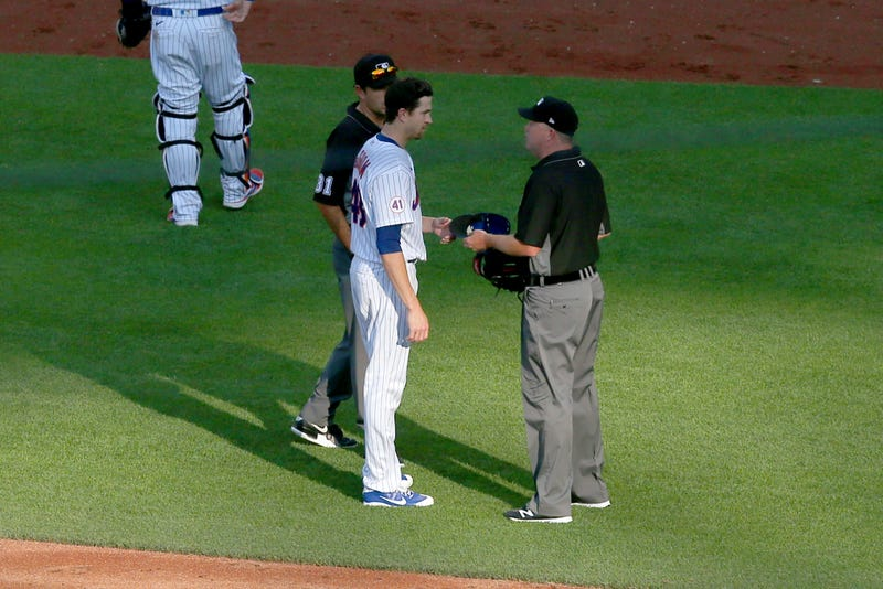Jun 21, 2021; New York City, New York, USA; Third base umpire Ron Kulpa (46) takes the hat of New York Mets starting pitcher Jacob deGrom (48) to check for foreign substances after the top of the fifth inning against the Atlanta Braves at Citi Field. Mandatory Credit: Brad Penner-USA TODAY Sports