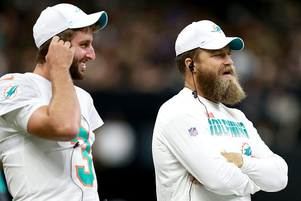 Dolphins QBs Josh Rosen (r) and Ryan Fitzpatrick watch from the sidelines.
