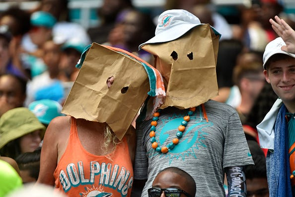 Ashamed Dolphins fans wear paper bags over their heads.