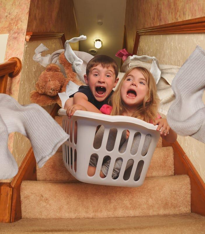 Kids sledding in laundry basket
