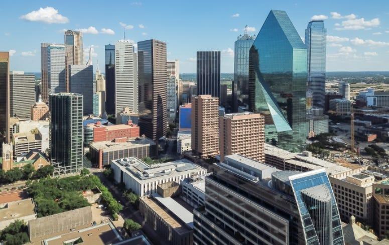 Aerial view Downtown Dallas skyscrapers under cloud blue sky. Midtown, freeway
