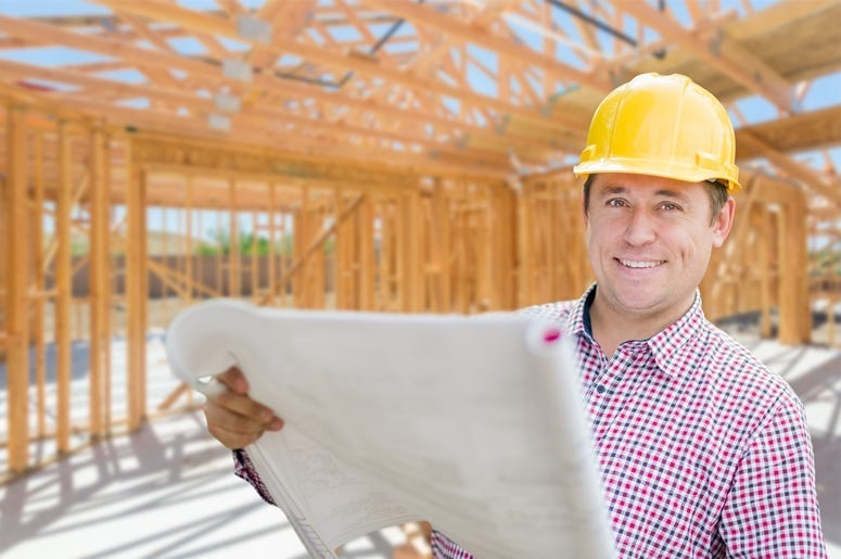 Contractor With Plans On Site Inside New Home Construction Framing
