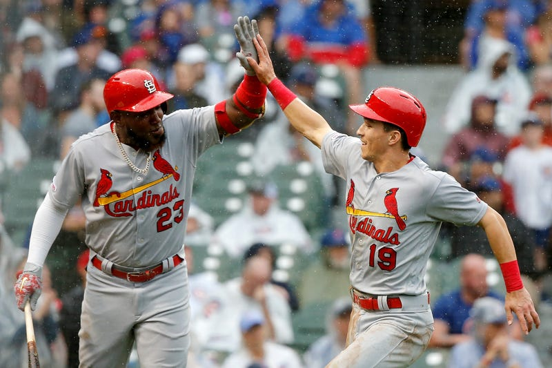 Tommy Edman celebrates scoring a run with Cardinals teammate Marcell Ozuna.