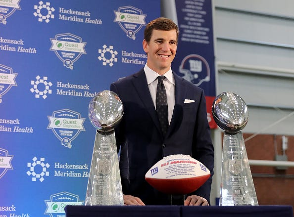 Eli Manning stands with his two Super Bowl trophies during his retirement announcement.