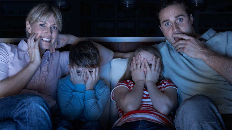 Family watching scary movie on the couch