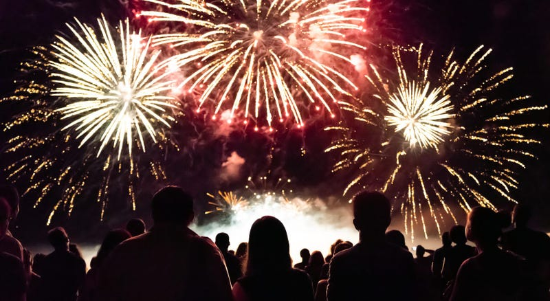 A fireworks display with people in foreground watching