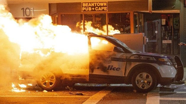 A Boston Police Department cruiser burns after being set on fire during  May 31 demonstrations in Boston.