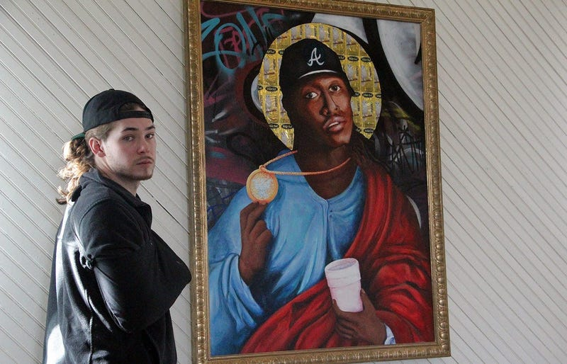 FREEKYBEAR stands next to his painting of Future at the TRAP CHAPEL pop-up art gallery in Atlanta