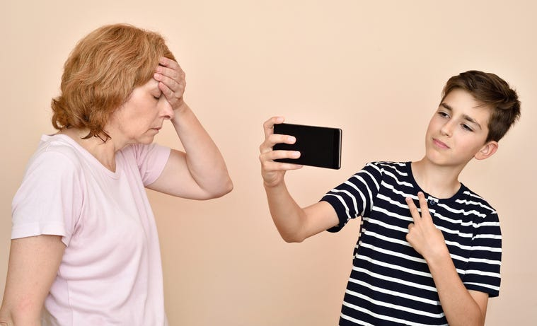 Son taking selfie while his dissatisfied mother is slapping her head with hand. Family and modern technology addiction concept.