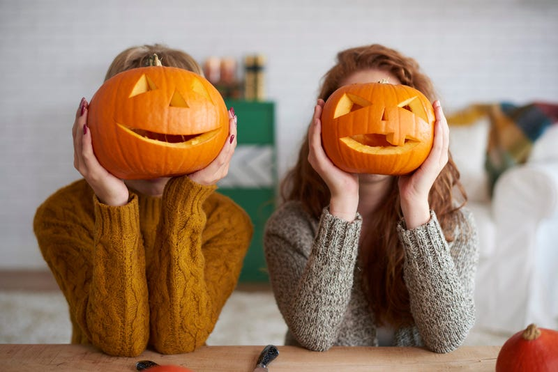 Two women showing Halloween pumpkins